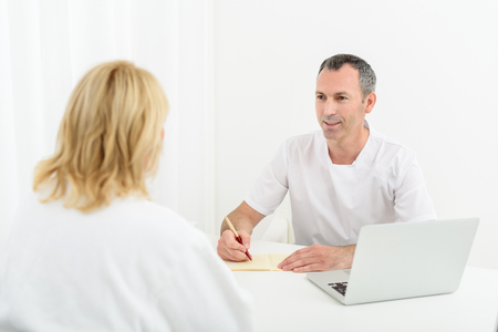 general practitioner: Joyful male general practitioner is writing diagnosis and smiling. He is sitting at table near laptop