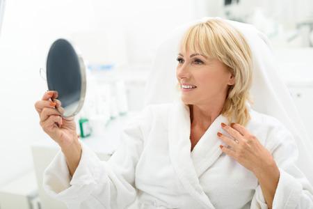 La donna senior allegra sta esaminando lo specchio e sta sorridendo. Lei è seduta su una sedia comoda al centro benessere Archivio Fotografico