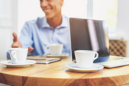 Joyful man has business meeting in cafe. He is sitting at table and smiling. Focus on cups of coffee and laptop