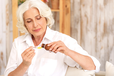 Ill mature lady is curing herself by syrup. She is sitting and pouring liquid into spoon with concern