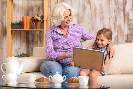 they are watching: Happy grandmother and granddaughter are watching photo in frame with interest. They are sitting on sofa and smiling. Old woman is embracing girl with love Stock Photo