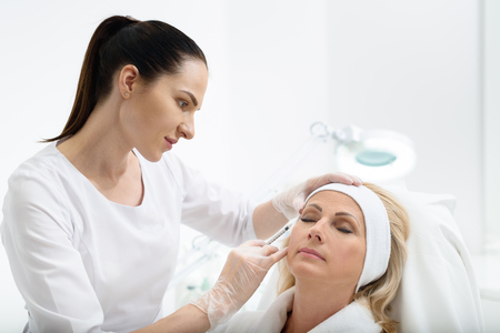 Professional doctor is injecting botox into female eye area with concentration. Calm senior woman is sitting with closed eyes