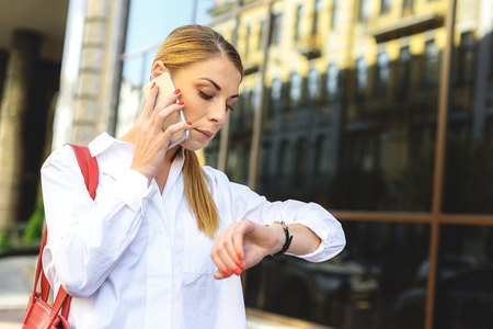 street shot: Cropped shot of beautiful busy girl checking time while talking on smartphone and walking on street Stock Photo