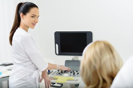 health professional: Female beautician working with ultrasound laser equipment at clinic. She is standing and smiling. Patient is sitting and looking at monitor Stock Photo