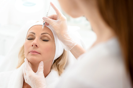lift hands: Skillful beautician is injecting botox into female forehead. Senior woman sitting with tranquility