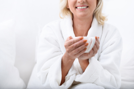 Relaxed mature woman is drinking coffee and smiling. She is sitting in white spa bathrobe