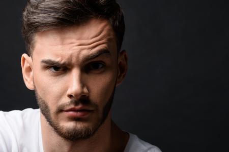 Portret van verrast man's gezicht met kopie ruimte tegen de donkere achtergrond
