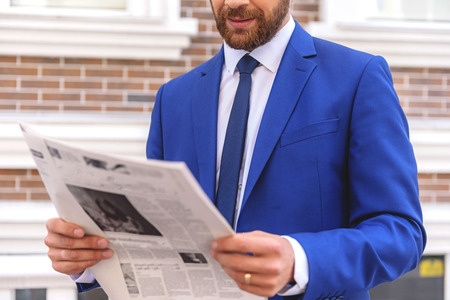 executive search: newspaper in hands of a bearded guy, close up Stock Photo