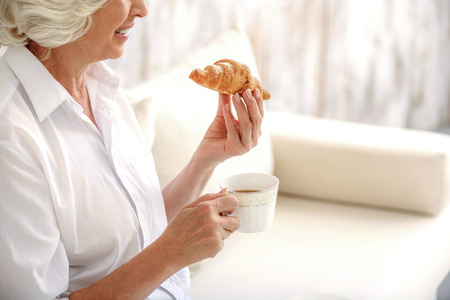 serine: Serine mature woman is enjoying breakfast in the morning. She is drinking tea and eating pastry. Woman is sitting on sofa and laughing Stock Photo