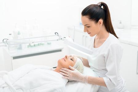 Profesjonalna kosmetyczka bada żeński skóry twarzy za pomocą lampy z koncentracją