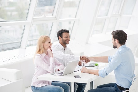 Two men shaking hands and looking at each other with smile while their coworker sitting near them