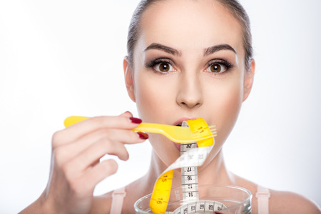 Fit young woman is eating tape measure from bowl. She is standing and looking at camera with aspiration. Isolated Stock Photo