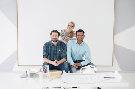 business pitch: Business team laughing together after successful business pitch, sitting near white board Stock Photo