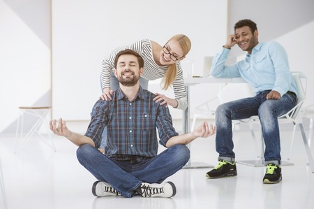 Smiling worker sitting on floor practicing yoga in lotus position with two colleague laughing at him in background