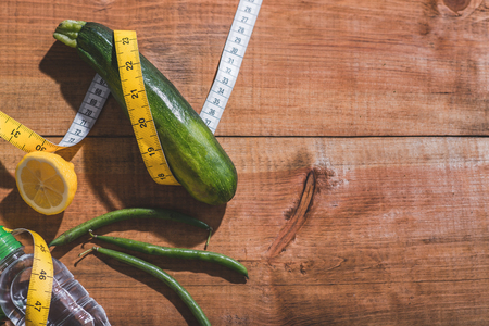 measured: Close up of squash, lemon, bottle of water and haricot measured tape on table Stock Photo
