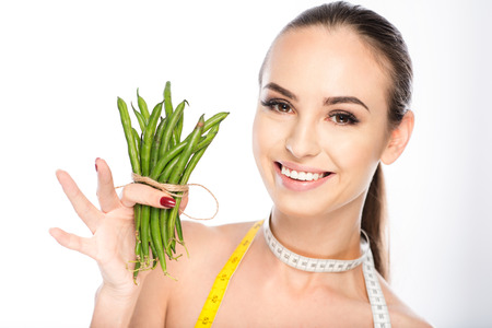 Slim young girl is showing green beans and laughing. She is carrying tape on neck. Isolated