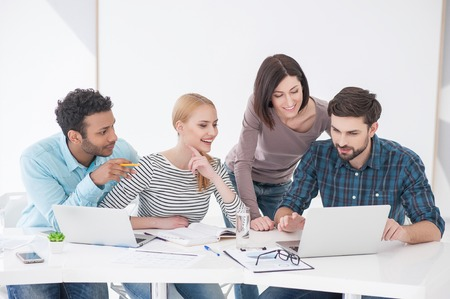 strategizing: Business people working on laptops around table at modern bright office indoors Stock Photo