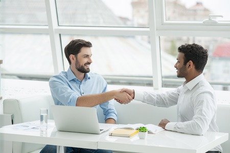Two confident young men shaking hands and smiling while sitting at desk in office near window Stock Photo