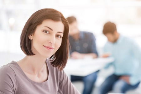 strategizing: Close up of attractive businesswoman with coworkers in background in their office
