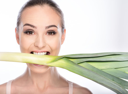 Slim young woman is standing and eating leek. She is holding it in mouth and looking forward with desire. Isolated Stock Photo
