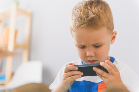 Close up shot of cute little boy holding smartphone in his hands and looking at it