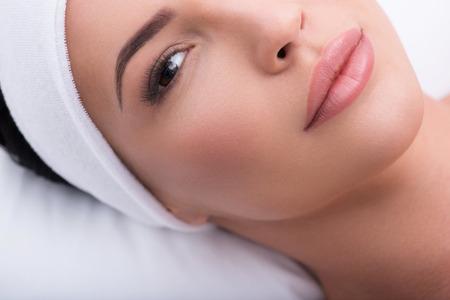 美容: 美麗的女人與加長的睫毛的頂視圖特寫鏡頭。她自信地躺著看著相機