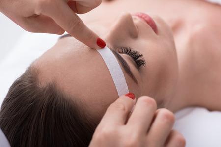 Close-up of beautician hands applying wax paper stick near female eyebrow
