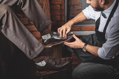 working man washing footwear on sitting customer, side view Stock Photo