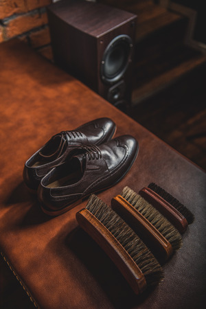 footware: elegant brogues on the table with accessories for shoe shining, close up Stock Photo