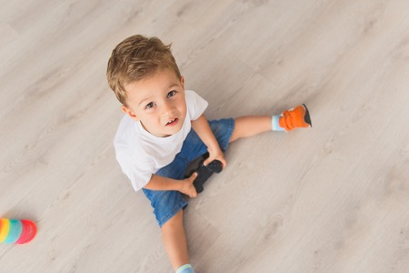 playfulness: Top view photo of small boy holding console in his hands and looking into camera Stock Photo