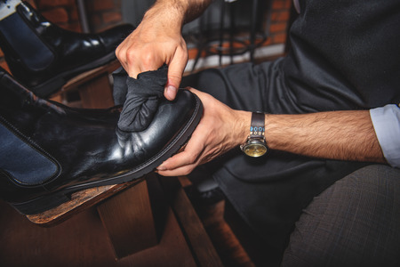 brogues: man wiping black brogues with a rag while on wooden shoe platform