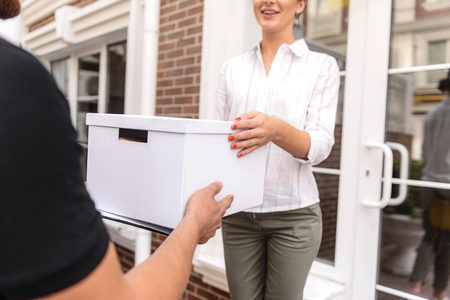 immediate: delivery man giving a box to the female customer Stock Photo