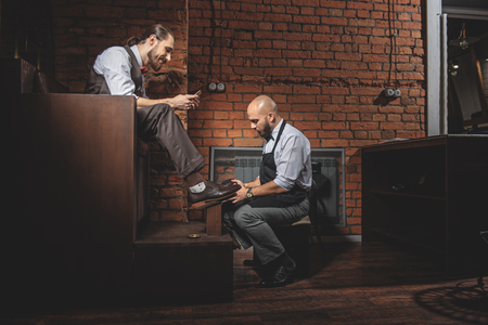 brogues: cheerful bearded man playing on his smartphone while his brogues being polished