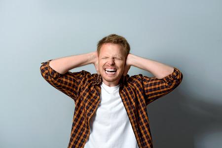 irrespeto: hombre tratando de ignorar el ruido fuerte y manteniendo sus oídos cerrados, concepto tinnitus Foto de archivo