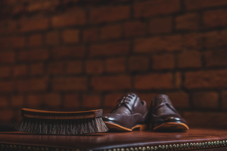 brogues: close up of a brush and pair of brogues on the old table Stock Photo