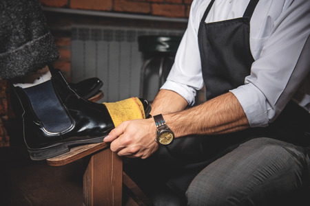 brogues: waxing brogues using a vintage shoe shine box with a polishing rag and a wooden shoe platform, side view Stock Photo