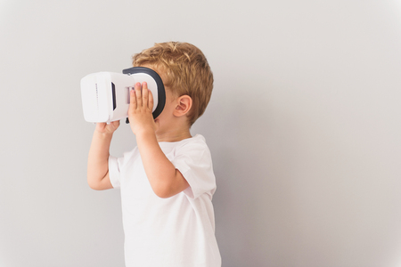 cropped shot: Cropped shot of little boy in virtual reality glasses playing game isolated on grey background