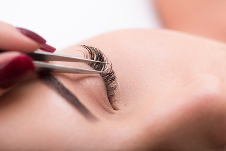 Close up cosmetician hand sticking artificial lash to female eye by tweezers Stock Photo