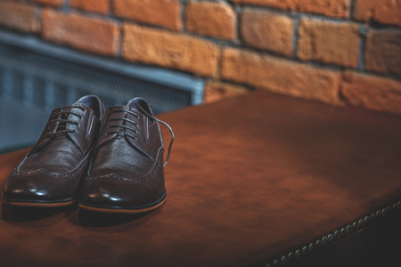 luxury mens footwear on the wood table over a brick background