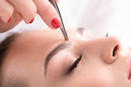 plucking: Close up of beautician hand plucking female eyebrow by tweezers