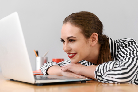 Joyful young businesswoman is looking at laptop and smiling. She is sitting at table and relaxing Reklamní fotografie