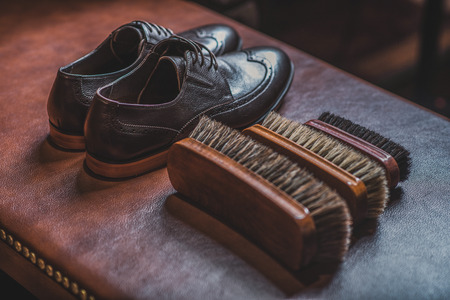 pair of footwear on the leather table next to tree brushes Stock Photo