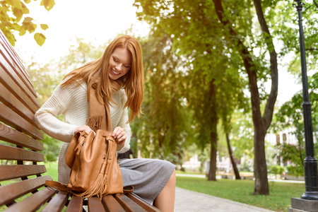 Cheerful young woman is resting in park. She is sitting on bench and opening her bag. Lady is smiling