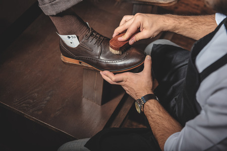 brogues: shoeshine man cleaning leather brogues with a horse brush