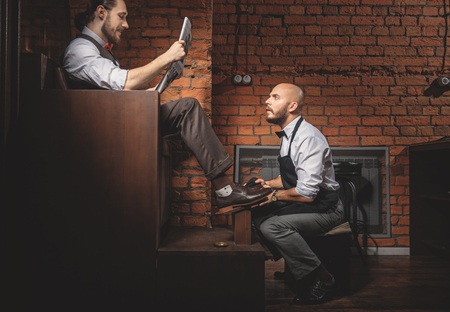 side view of a curious worker reading newspaper of client while working Stock Photo