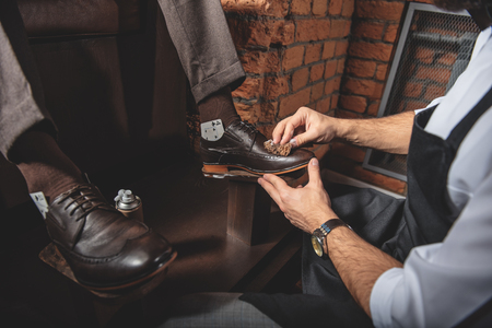 brogues: front view of brogues being polished by artisan indoors, close up