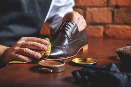 hands of a man waxing leather shoes on the table Stock Photo