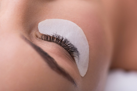 Close up of female closed eye with artificial lashes over small special paper