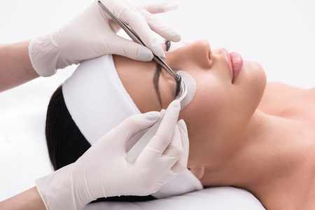 Close up of young woman lying and getting eyelash extension procedure by cosmetician Stok Fotoğraf