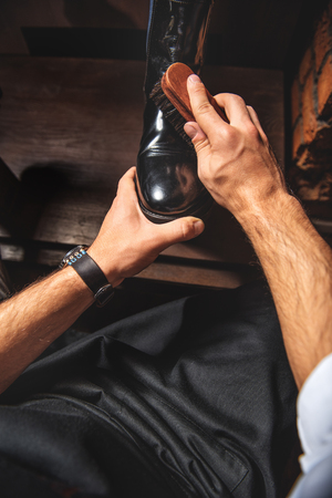 first-person view of a man polishing black and shiny footwear Stock Photo